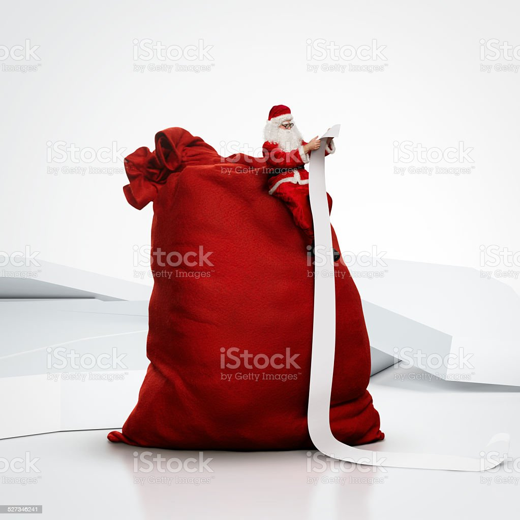 Santa sitting on huge sack and reading long list stock photo