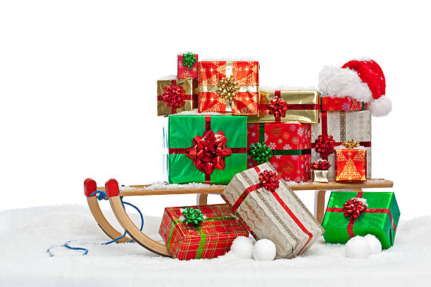 Santa sledge loaded with gift wrapped presents A sledge loaded with gift wrapped Christmas presents and a Santa hat, sitting on snow against a white background. sleigh stock pictures, royalty-free photos & images