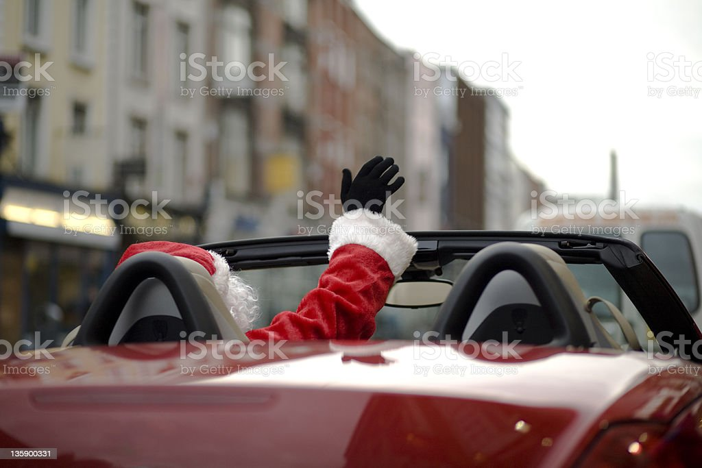 Santa waiving from his red deliviery car stock photo
