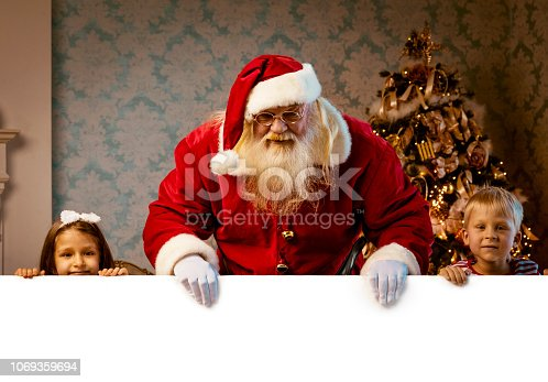 istock Santa with blank empty white poster 1069359694