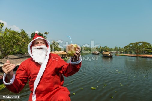 Santa Clous holding fresh coconut and looking at camera. In background many house boats sail down the river in backwaters against palms background and blue sky In Alappey, Kerala, India. Kerala state, with a large network of inland canals earning it the sobriquet