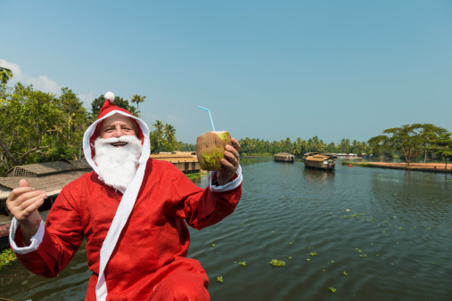 Santa Clous holding fresh coconut and looking at camera. In background many house boats sail down the river in backwaters against palms background and blue sky In Alappey, Kerala, India. Kerala state, with a large network of inland canals earning it the sobriquet \