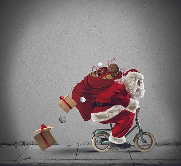 santaclaus auf dem fahrrad - schnelles weihnachtsessen stock-fotos und bilder