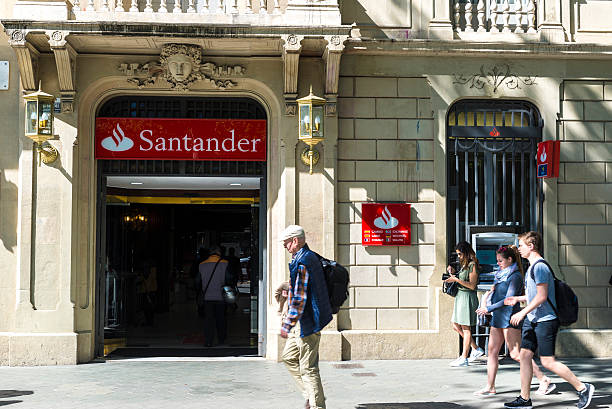 Santander bank branch in Barcelona Barcelona, Spain - May 4, 2016: Santander bank branch located on Passeig de Gracia, one of the most expensive streets in Europe. A woman just take money from the cashier while people walk down the street gracia baur stock pictures, royalty-free photos & images