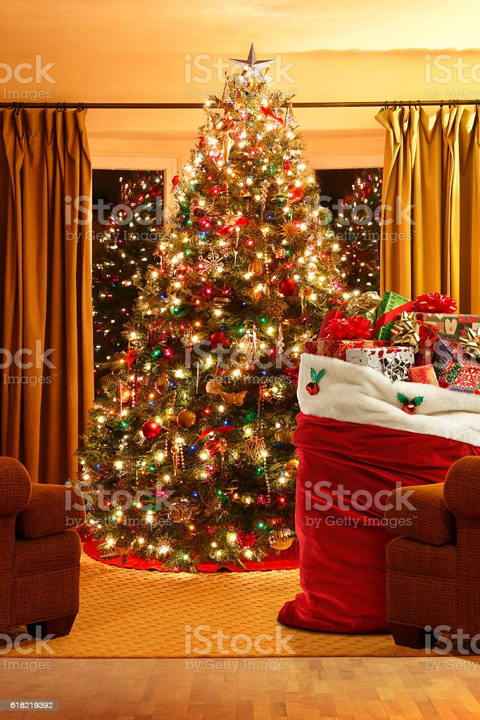 Santa's Bag Full Of Presents In Front Of Christmas Tree stock photo