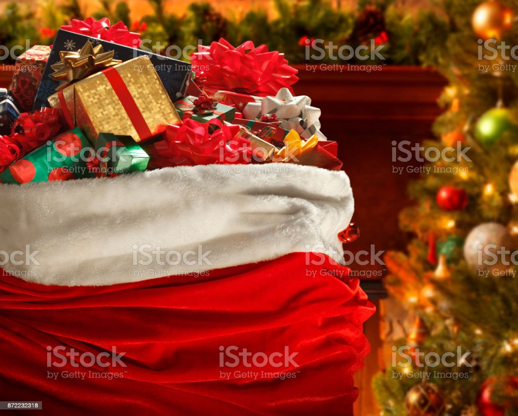Santa's Bag In Front Of Christmas Tree And Fireplace stock photo