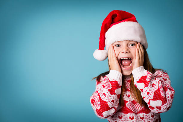 santa's excited little helper wearing hat and christmas sweater - ugly girl stock photos and pictures