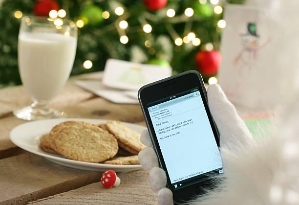 santa чтение его почты в современном стиле - hand holding phone стоковые фото и изображения