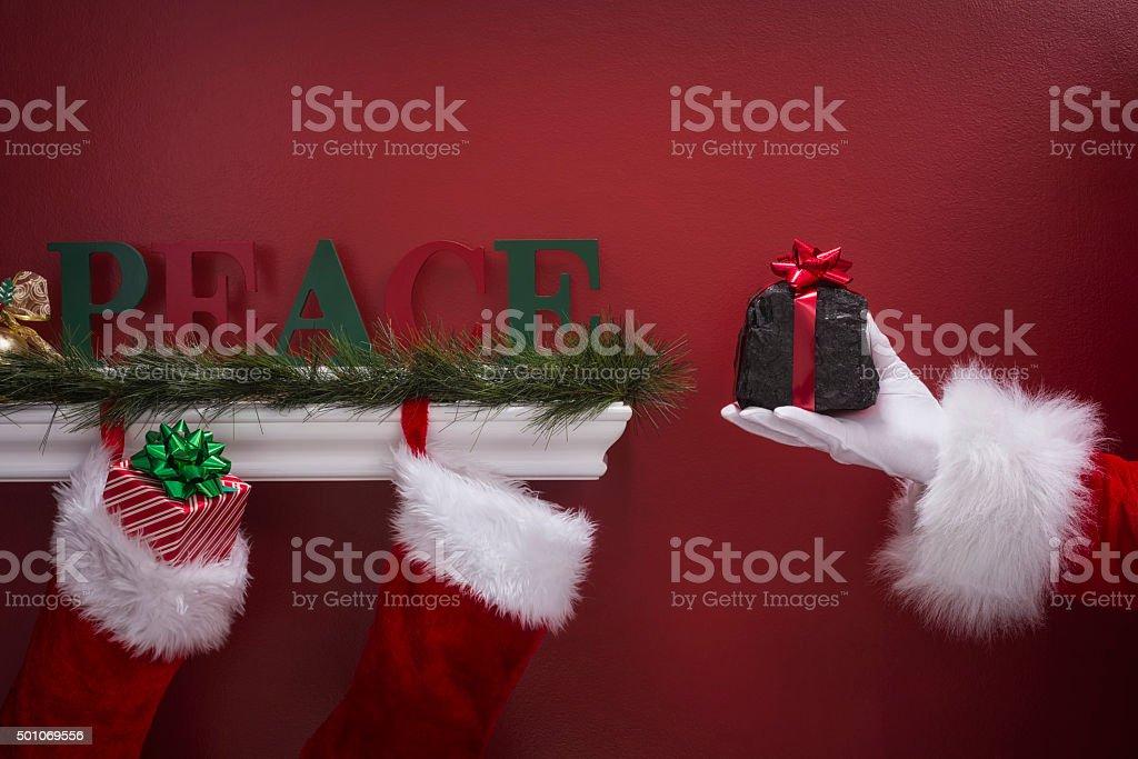 Santa's hand holding coal next to Christmas Stockings stock photo