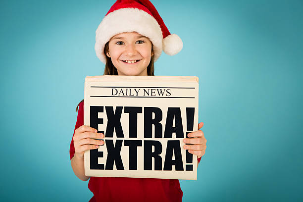 Santa's Happy Little Helper Holding Up Newspaper Color image of a young girl, wearing a Santa hat and holding up the front page of a newspaper. front page stock pictures, royalty-free photos & images