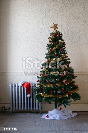 Santa hat on radiator beside artificial tree in old fashioned space.Related images: