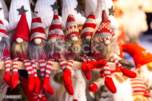 Close up color image depicting Santa's little elfin helpers Christmas decorations in a row and for sale at a Christmas market. They are sitting on a shelf and are wearing red stripy stockings and pointed hats.