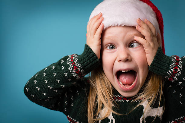 santa's stressed little helper wearing hat and christmas sweater - ugly sweater stock photos and pictures