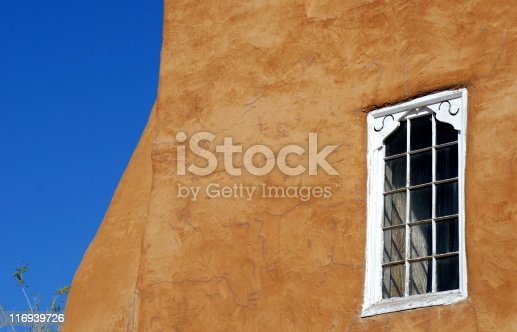 Tight shot of an old adobe mission church in downtown Sante Fe, New Mexico.  Clear blue sky contrasts with the hue of the adobe.