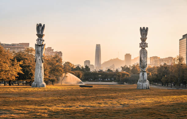 Santiago skyline at Araucano Park and chemamules traditional mapuche sculptures - Santiago, Chile stock photo