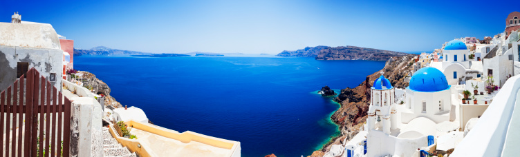 Panorama of Santorini caldera with famous Orthodox churches with blue domes in village Oia (Ia). XXXL wide panorama, stitched from 8 images Canon 5DMkII. Click for more images: http://santoriniphoto.com/Template-Greek.jpg