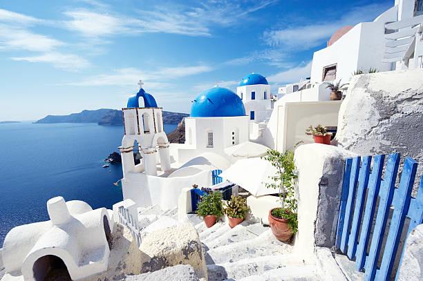 santorini greece bright morning blue gate overlooking mediterranean sea - santorini stock photos and pictures
