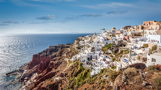 Panorama view towards Oia with the iconic white and blue typical greek Santorinia Houses, Windmill and orthodox church at the rocky mediterranean coast of Santorini. Oia, Santorini Island, Cyclades Islands, Greece, Europe.