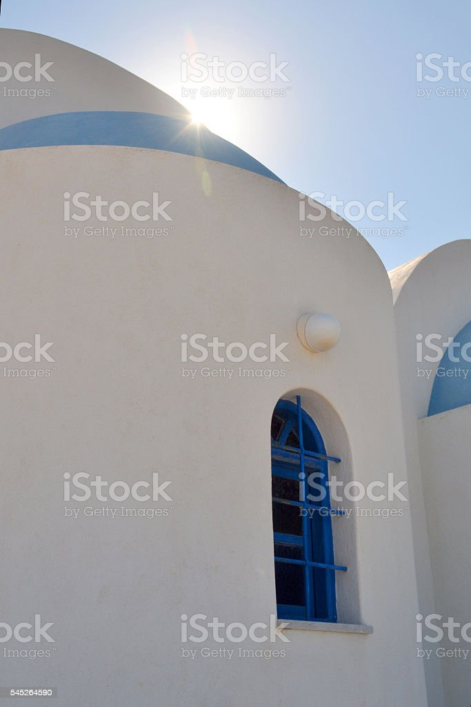 Santorini white building with blue dome and sunlight stock photo