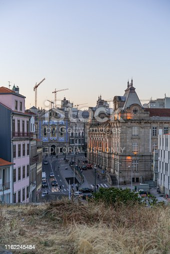 Porto, Portugal - June 12, 2019:  People on Avenida Dom Afonso Henriques and the historical Sao Bento Train Station. At the end of the road is visible the Igreja de Santo Antonio dos Congregados with the typical blue azulejos.