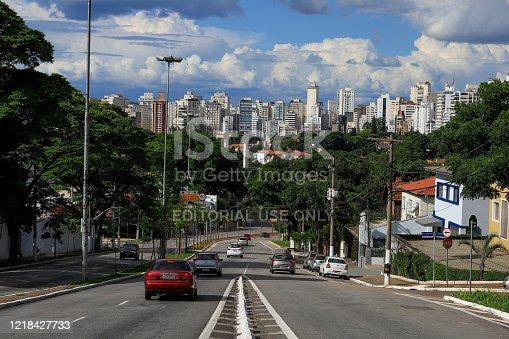 Sao Paulo, Brazil - Feb 08, 2020 - Cars traffic in avenue with skyline of Sao Paulo city with blue sky and clouds on background. Sao Pauo, Brazil