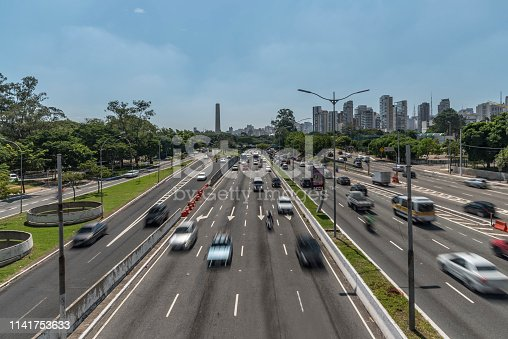 Wide four-lane highway with speeding car traffic, with trees on both sides and blue skies with sparse clouds and the skyline of São Paulo at the horizon