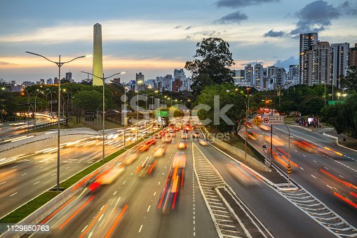 Cars and light trails are blurred on modern city street, Brazil