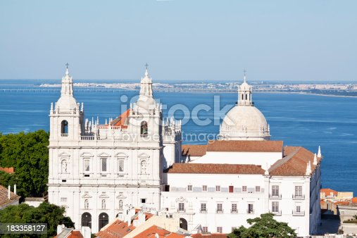 The Sao Vicente de Fora Monastery in the foreground was founded in 1147 for the Augustinian Order with the 17th century Santa Engracia Church behind stand beside the River Tagus in Lisbon. The 17.2 km Vasco da Gama bridge spans the Tagus River estuary in the background. Good copy space.