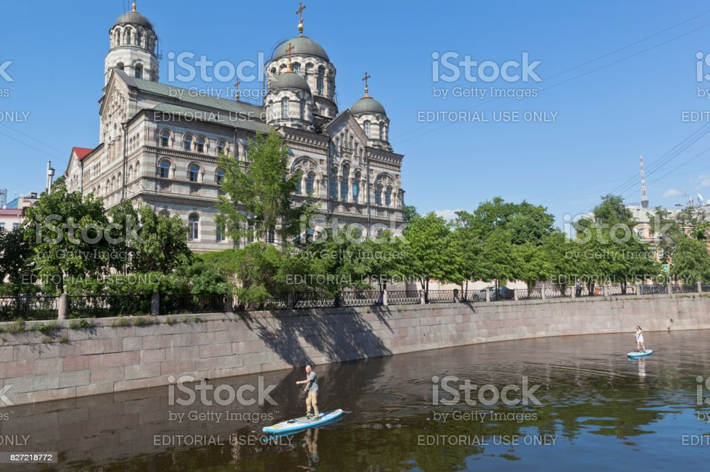 Sapsurfing along the Karpovka River against the background of St. John's Convent in St. Petersburg stock photo