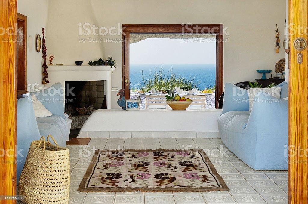 Sardinian house entrance, carpet, sofa, fireplace, terrace on the sea stock photo