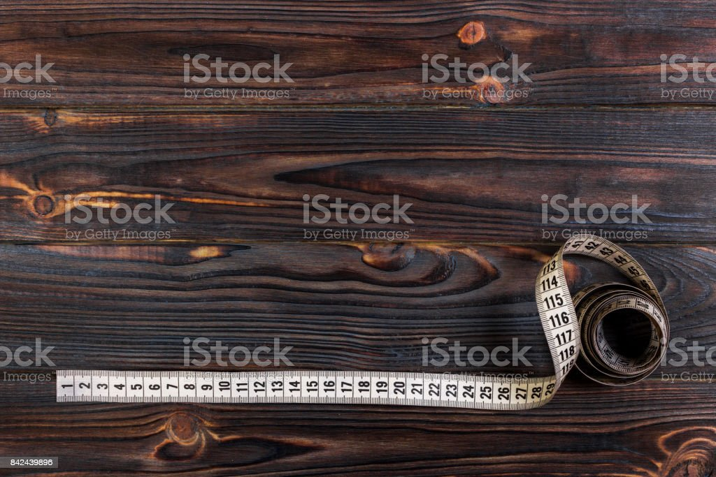 sartorial meter and scissors on the old wooden background stock photo