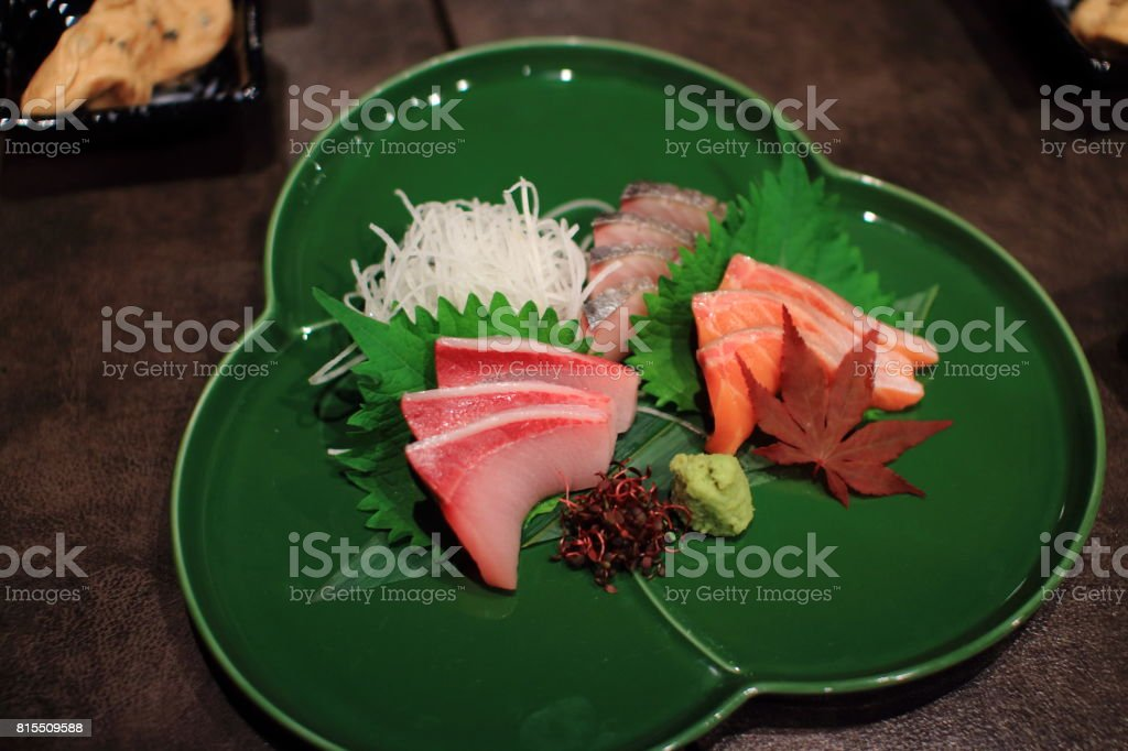 Sasimi dish. Luxury Japan raw fish on ceramic plate on wood table in a traditional Japanese restaurant. stock photo