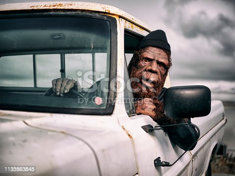 A Bigfoot Sasquatch character driving an old pickup truck.