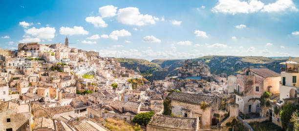 Sassi di Matera, Basilicata, Italy Panoramic view of the ancient town of Matera (Sassi di Matera) on a sunny day with blue sky and clouds, Basilicata, southern Italy matera italy stock pictures, royalty-free photos & images
