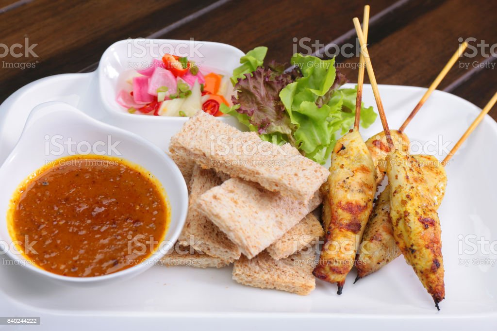 Satay Chicken , Sate Ayam with Peanut Sauce and bread , Asian skewers famous food stock photo