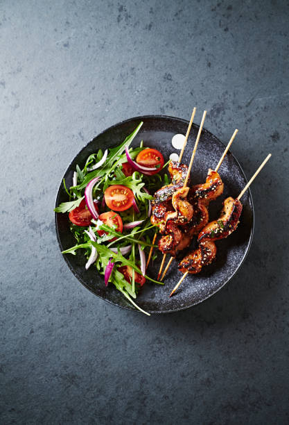Satay chicken skewers with salad stock photo