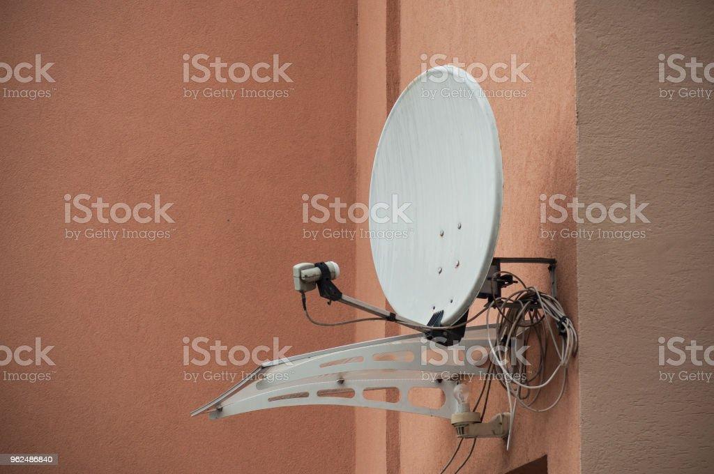 satellite antena on orange home facade stock photo