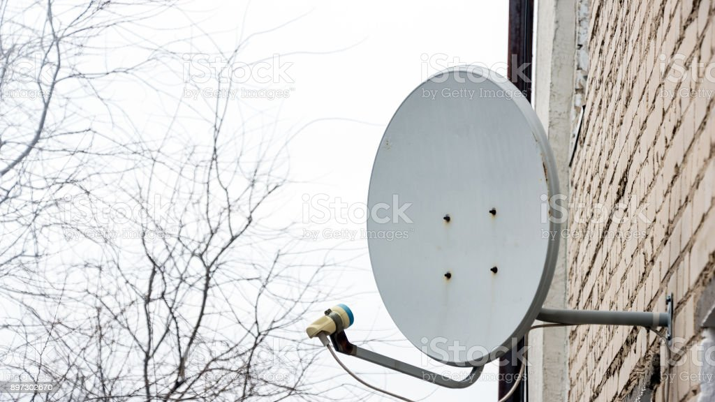 Satellite antenna dish on the brick wall stock photo