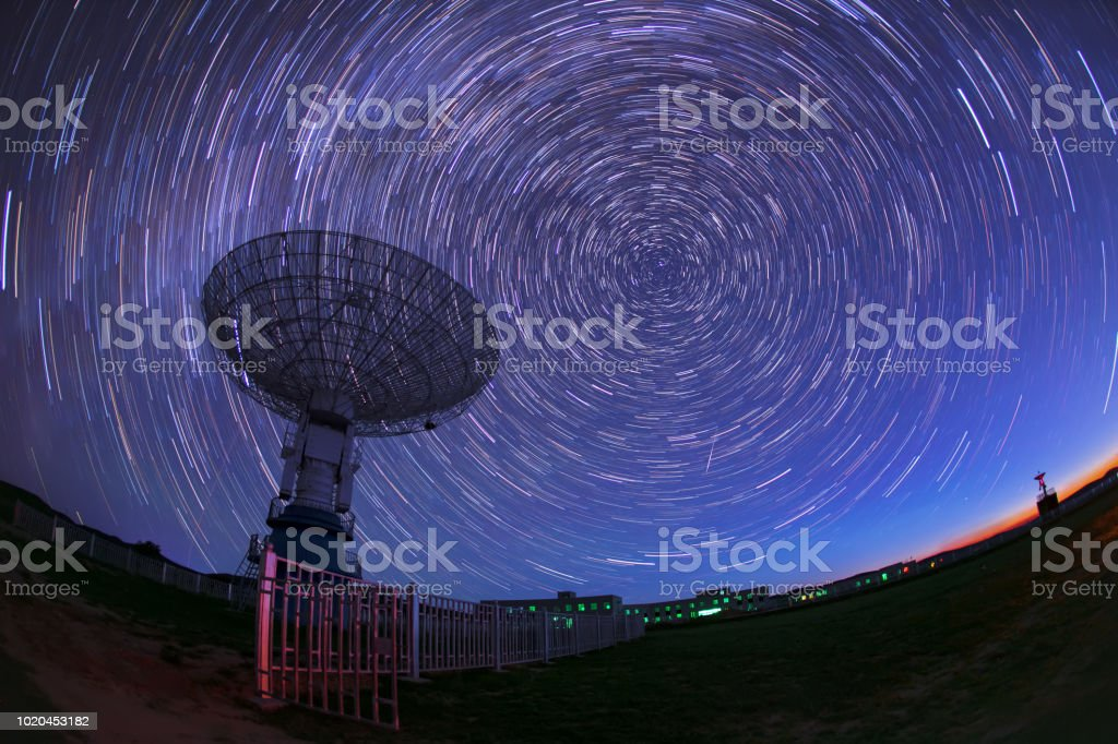 satellite antenna radio telescope on the background of stellar tracks stock photo