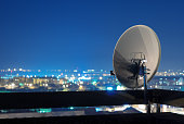 istock Satellite dish antenna on top of the building at night. 469038268