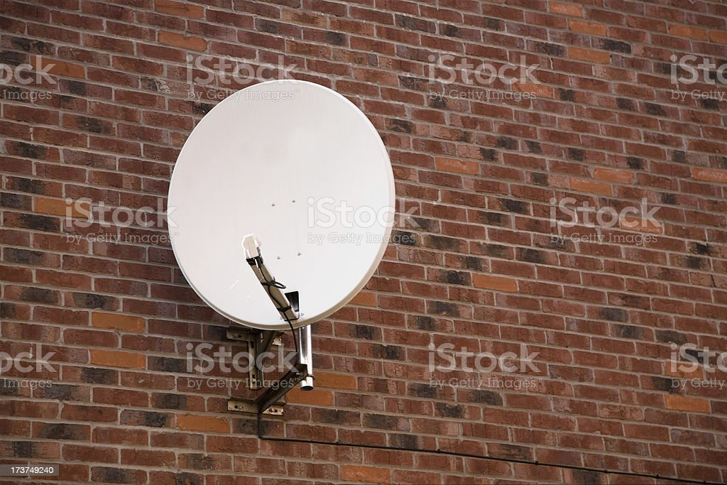 Satellite Dish Attached to Redbrick Wall-More in lightbox below royalty-free stock photo