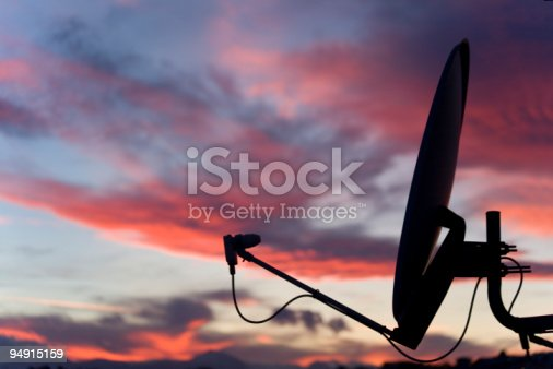 Satellite dish against a pink tinged sky. Other images in: