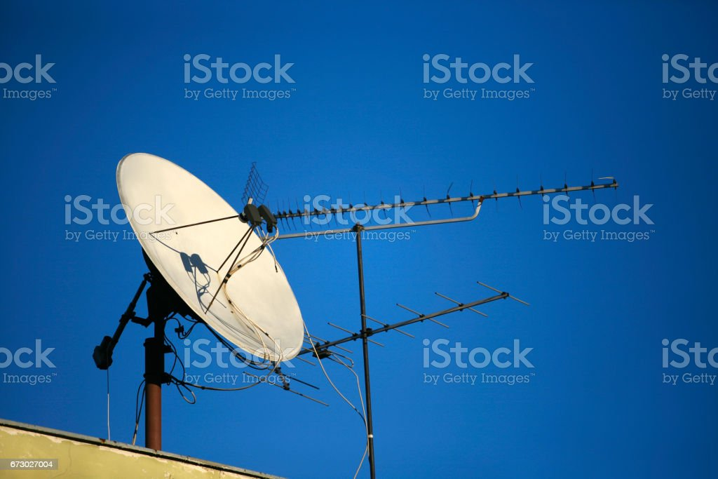Satellite dish of TV on a roof on a background of the sky stock photo