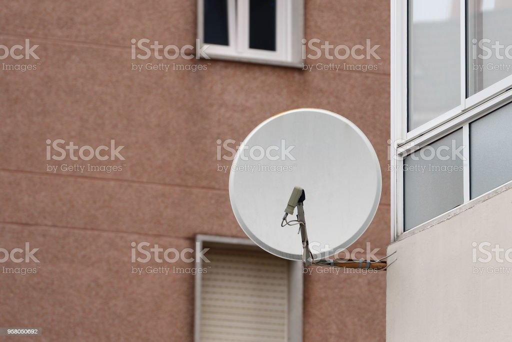 satellite dish on a building wall stock photo