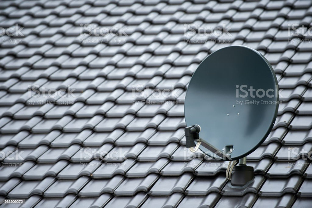 satellite dish on a new black roof stock photo