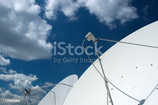 A satellite dish with clouds as a background.