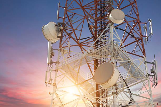 Satellite dish telecom tower at sunset stock photo