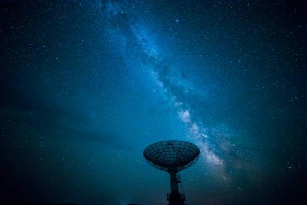 Antena parabólica sob um céu estrelado - foto de acervo