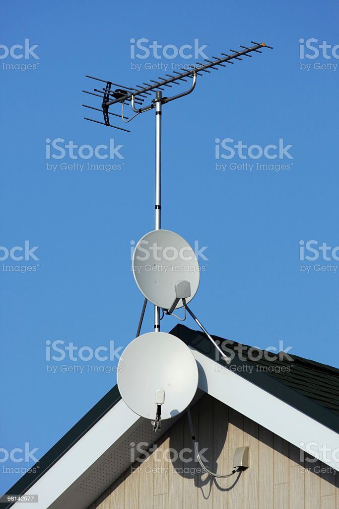 Satellite dishes and TV antenna on blue sky royalty-free stock photo