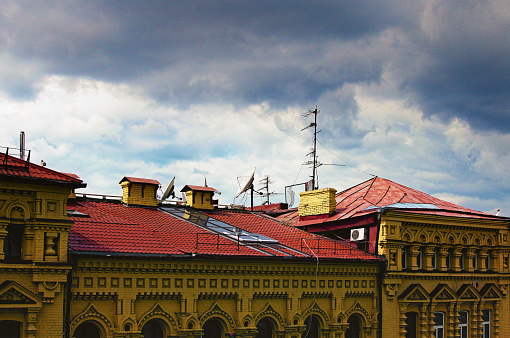 Satellite dishes and TV antennas on the house roof with a cloudy sky. Red tile roof with different TV antennas and satellite dishes.